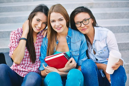 Three casual teen girls looking at camera with smiles photo