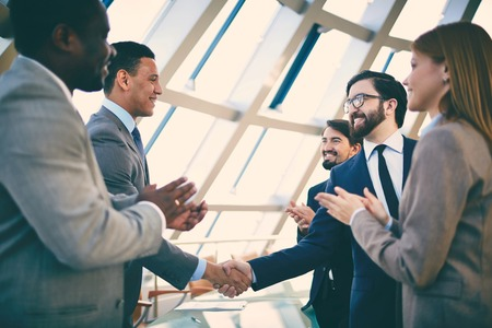 congratulating: Group of business people congratulating their handshaking colleagues after signing contract Stock Photo