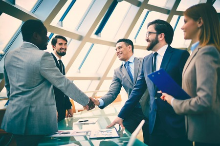 agreement: Group of business people looking at their colleagues handshaking in office