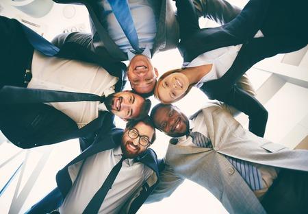 보기에서 머리에 서있는 동안 카메라를 찾고 정장을 입고 친절한 기업인 그룹
