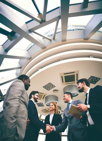 Twee gelukkige zakenlieden handshaking met hun collega's in de buurt van door