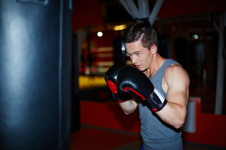 boy boxing: Male boxer in boxing gloves training in sports gym Stock Photo