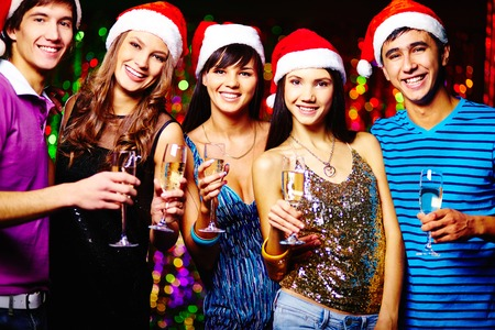 Group of joyful friends in Santa caps toasting at party and looking at camera photo