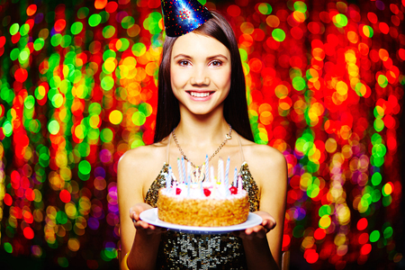 Lovely brunette with birthday cake looking at camera on sparkling background photo