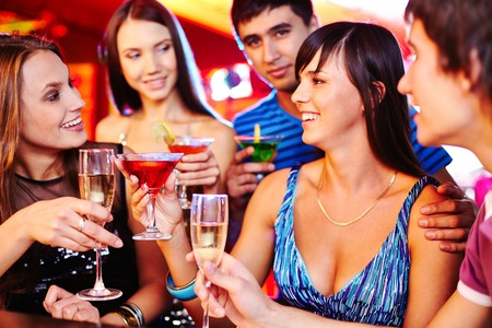 Cheerful girls and guys with martini and champagne having fun at party photo