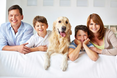 a young family: Row of cheerful family members at home Stock Photo