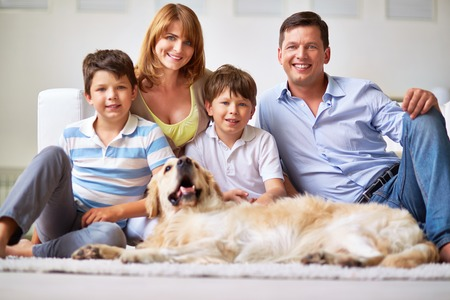 Portrait of happy family members and restful dog photo