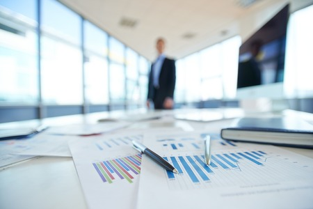 Papers with financial data on office table Stockfoto