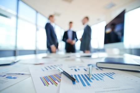 Documenten op kantoor tafel en drie mannen praten op de achtergrond
