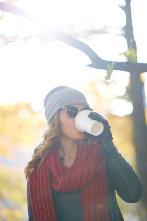 Woman drinking coffee in the street photo