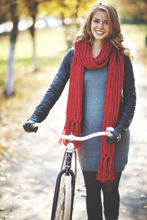Young stylish woman walking with bike in autumn photo