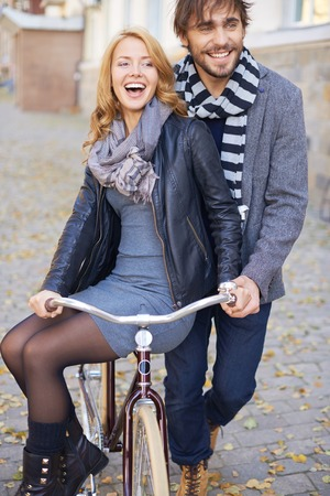peo: Man carrying his girlfriend on bicycle Stock Photo