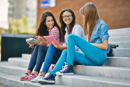 Three teenage girls communicating outdoors
