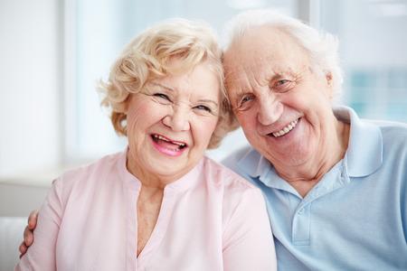 mujeres ancianas: Retrato de una pareja de ancianos positivo mirando la cámara y sonriendo Foto de archivo