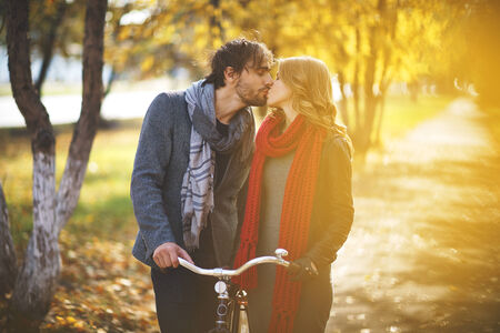 Young couple kissing in autumn park photo