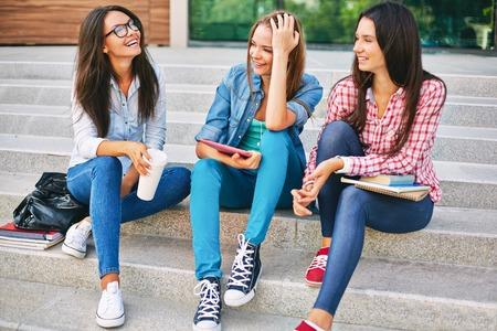 Three teenage girls talking on school steps photo