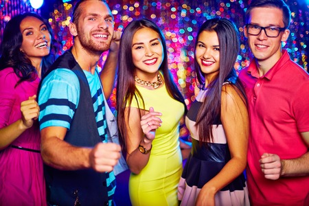 Portrait of five friends dancing at disco party photo