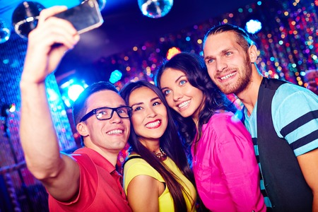 Young people taking selfie at party