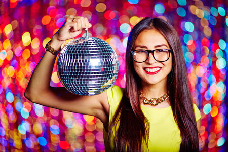 Portrait of a girl in glasses holding disco ball photo
