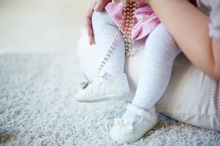 ni�as peque�as: Las piernas de un ni�o sentado en el regazo de su madre Foto de archivo