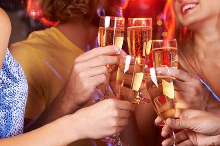 Five hands raising champagne flutes in a toast Archivio Fotografico
