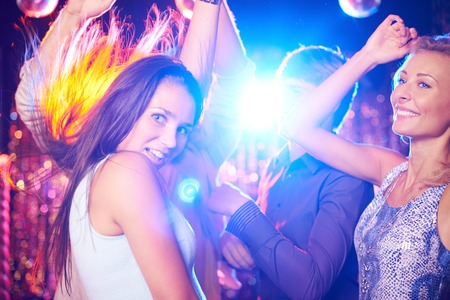 Energetic young people dancing in night club photo