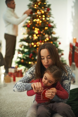 Pretty female showing her little daughter how to knit with man decorating xmas tree on background photo
