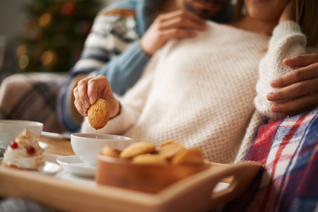 restful: Young restful female with biscuit being embraced by a man during tea time