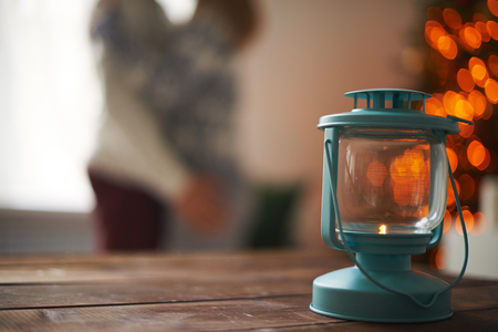 Lantern on wooden table on background of lovers photo