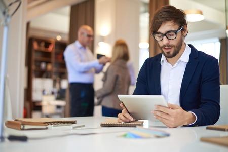 Knappe zakenman in casual netwerken op de achtergrond van zijn partners Stockfoto