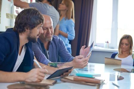 personas sentadas: Hombre de negocios maduro con touchpad que muestra sus ideas colega para nuevo proyecto Foto de archivo