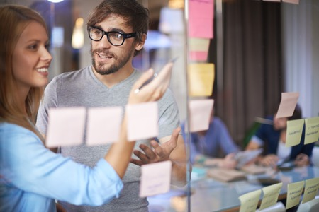 personas comunicandose: Colegas masculinos y femeninos que discuten las notas sobre los recordatorios de papel en la oficina