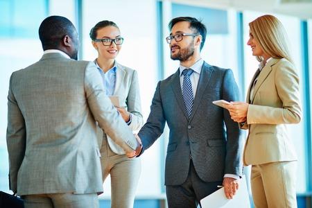 saludo de manos: Dos hombres de negocios apret�n de manos despu�s de firmar contrato con sus colegas mujeres en las inmediaciones Foto de archivo