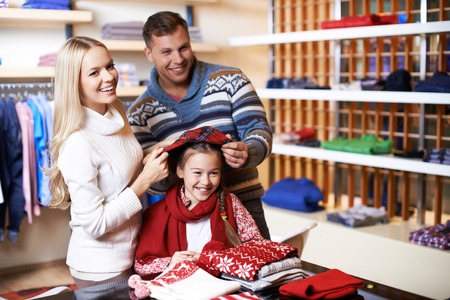 Portrait of young parents trying cap on their daughter in department store photo
