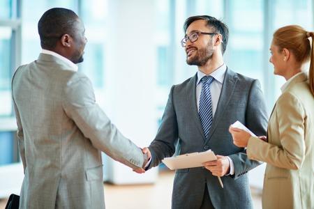 두 기업인 계약을 만들고, 근처에 서있는 그들의 여성 동료