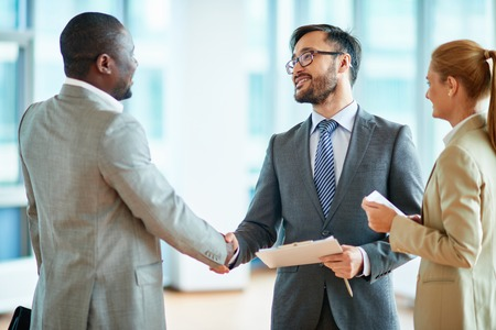 partnerships: Two businessmen making agreement, their female colleague standing near by