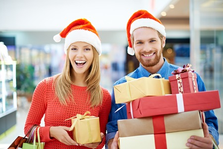 Happy couple of shoppers buying Christmas presents photo