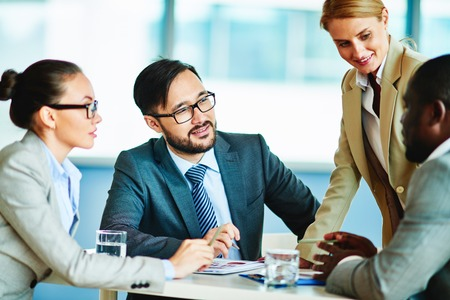 Several confident businesspeople interacting at meeting