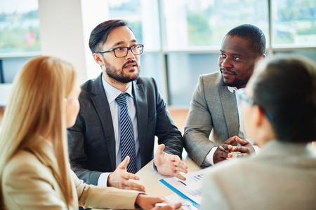 Ernstige zakenman van Aziatische afkomst spreken, terwijl zijn collega's naar hem te luisteren op de vergadering van Stockfoto