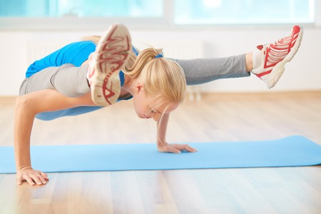 Agile blond girl doing yoga exercise in gym Stock Photo