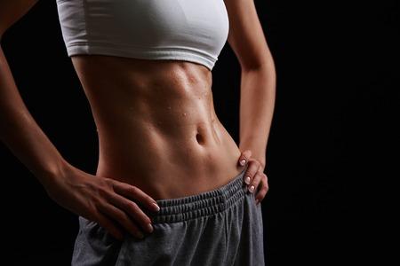 vientre femenino: Cuerpo femenino húmedo en ropa deportiva Foto de archivo