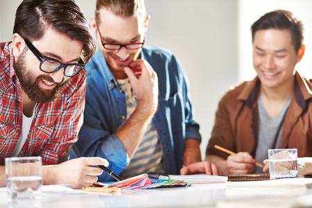 colaboracion: Tres dise�adores alegres que eligen colores de la paleta Foto de archivo