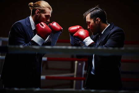 business rival: Business boxers attacking one another