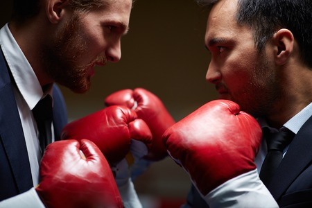business rival: Two furious businessmen in boxing gloves attacking one another Stock Photo