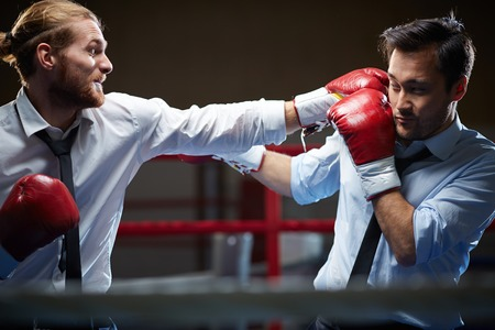 Competitive businessman giving his rival a facer
