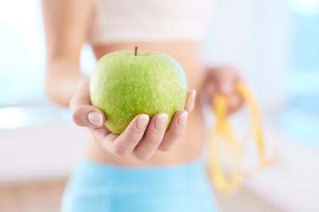 女性が保有する新鮮な青リンゴのクローズ アップ