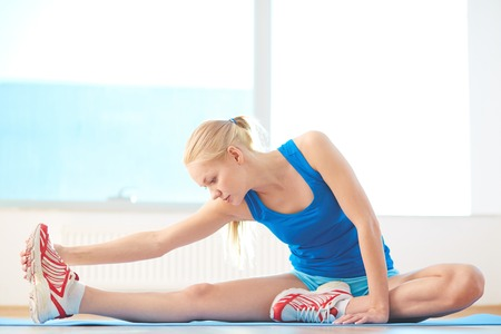 activewear: Sporty woman in activewear doing stretching exercise in gym