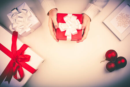 Red giftbox in female hands with other boxes, snowflake in frame and decorative toy balls near by photo