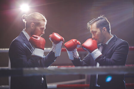 business game: Businessmen in suits and boxing gloves attacking one another