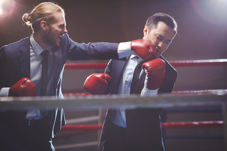 Powerful businessman in suit and boxing gloves attacking his rival photo